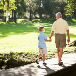 Grandfather and grandson walking in the garden